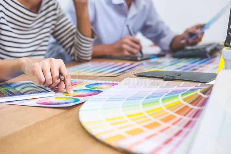 Δημιουργικός γραφικός σχεδιαστής δύο συναδέλφων που εργάζεται στο χρώμα επίλεκτο στοκ εικόνες με δικαίωμα ελεύθερης χρήσης