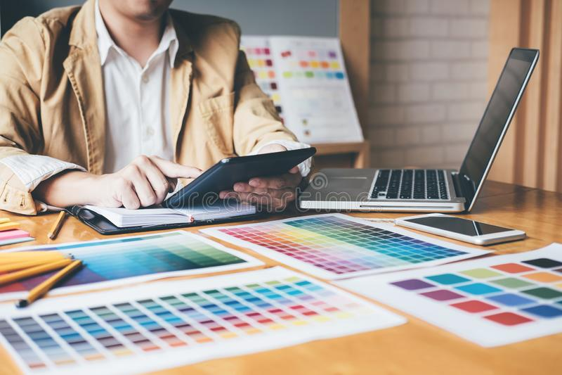 Δημιουργικός γραφικός σχεδιαστής που χρησιμοποιεί την ταμπλέτα γραφικής παράστασης στην επιλογή του colo στοκ φωτογραφία
