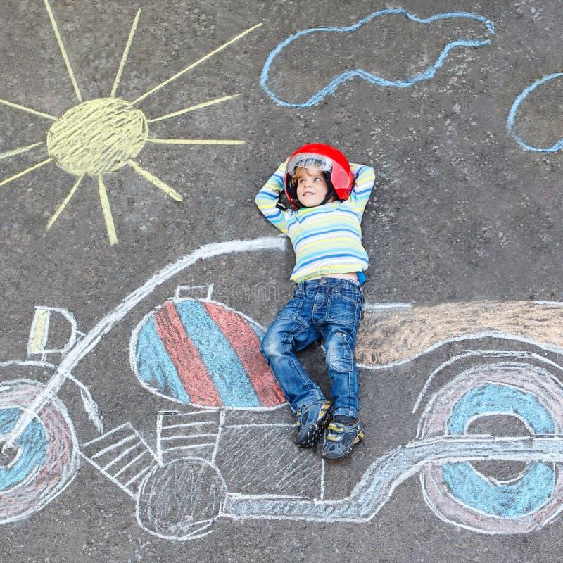 Δημιουργικός ελεύθερος χρόνος για τα παιδιά: Αστείος λίγο παιδί τεσσάρων ετών στο κράνος που έχει τη διασκέδαση με το σχέδιο εικό στοκ φωτογραφίες