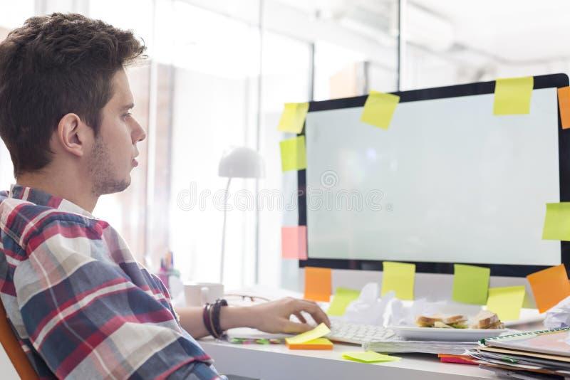 Δημιουργικός επιχειρηματίας που εξετάζει το όργανο ελέγχου υπολογιστών τις συγκολλητικές σημειώσεις που κολλιούνται με σε το στοκ εικόνα με δικαίωμα ελεύθερης χρήσης