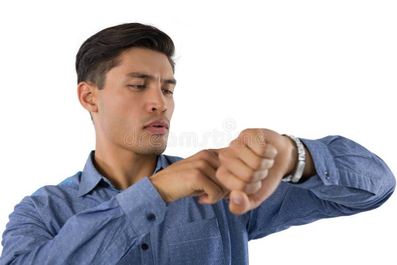 Δημιουργικός επιχειρηματίας που εξετάζει το wristwatch στοκ φωτογραφία με δικαίωμα ελεύθερης χρήσης