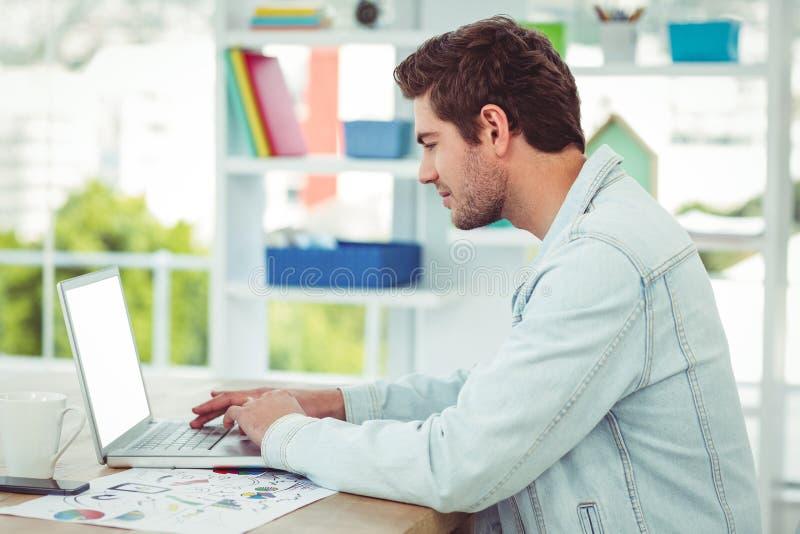 Δημιουργικός επιχειρηματίας που εργάζεται στο lap-top του στοκ φωτογραφία