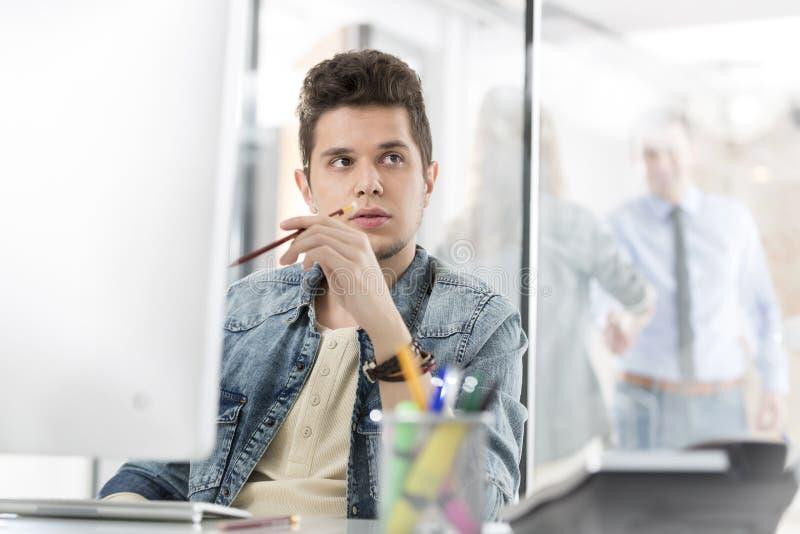 Δημιουργικός επιχειρηματίας που κοιτάζει μακριά καθμένος στο γραφείο υπολογιστών στοκ εικόνες