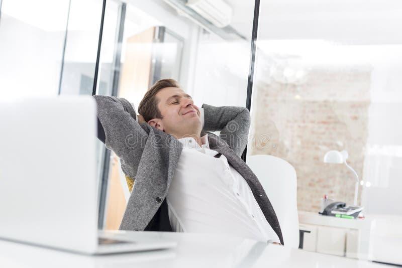 Δημιουργικός επιχειρηματίας που στηρίζεται στο γραφείο στην αρχή στοκ φωτογραφία με δικαίωμα ελεύθερης χρήσης