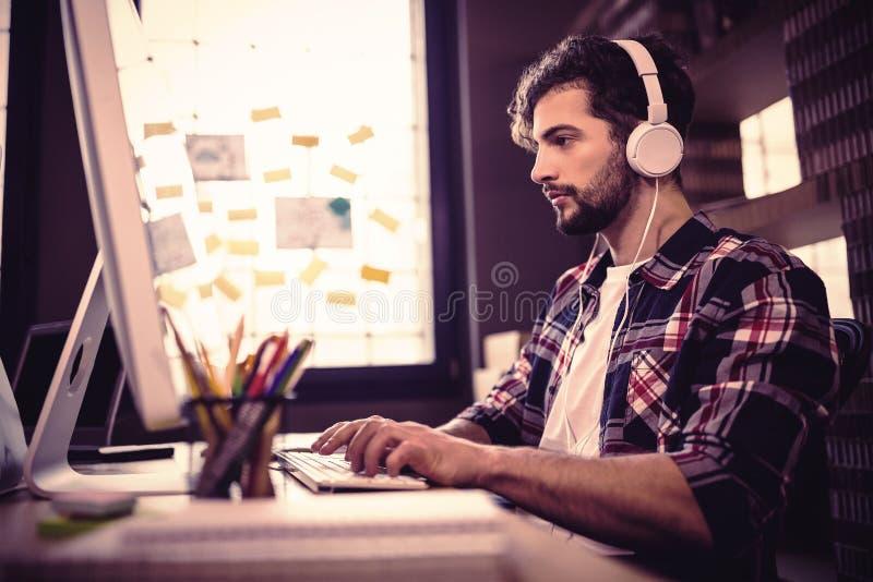 Δημιουργικός επιχειρηματίας που χρησιμοποιεί τον υπολογιστή ενώ μουσική ακούσματος στοκ εικόνες