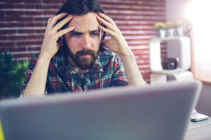 Δημιουργικός επιχειρηματίας Fraustrated που εξετάζει το lap-top στοκ εικόνα
