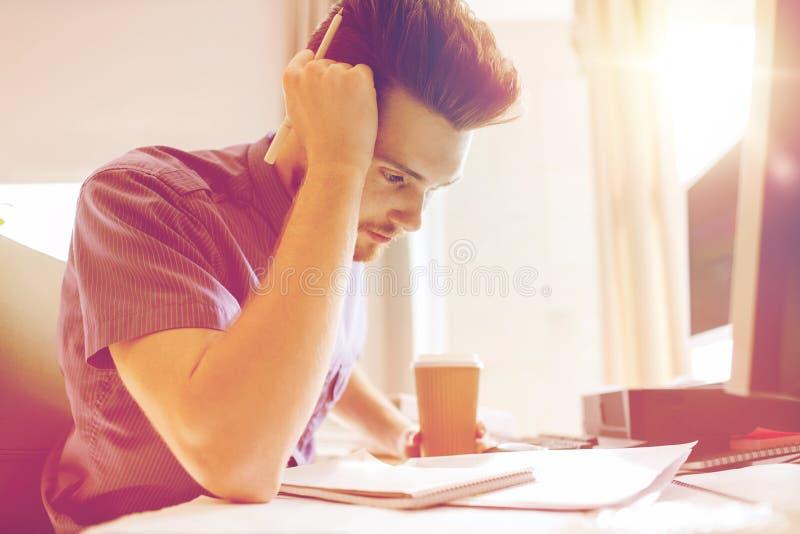Δημιουργικός εργαζόμενος γραφείων αρσενικών με τη σκέψη καφέ στοκ εικόνες