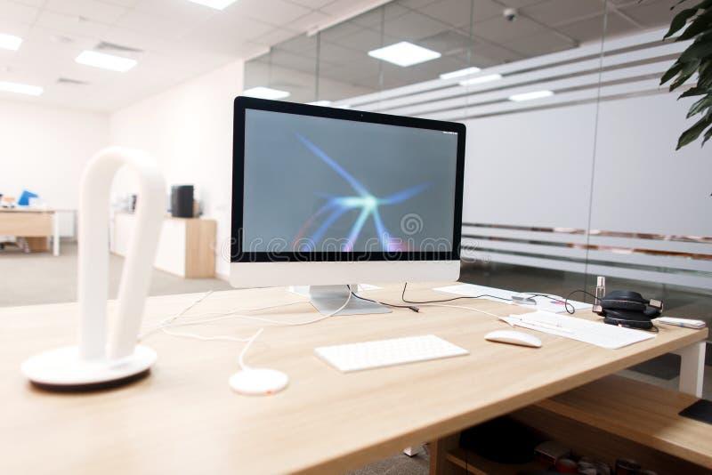 Δημιουργικός εργασιακός χώρος με τον υπολογιστή στον άσπρο πίνακα στην αρχή στοκ εικόνες