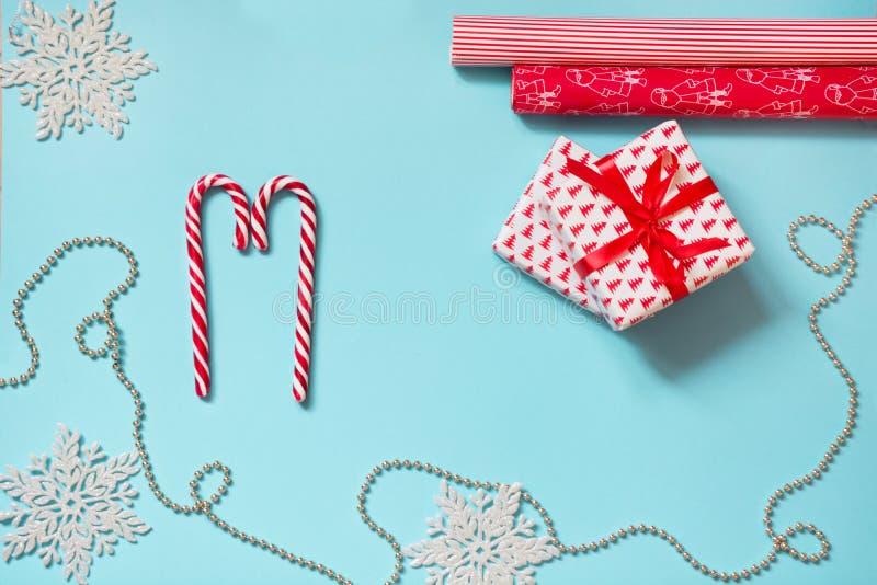 Δημιουργικός εργασιακός χώρος Χριστουγέννων με το δώρο, snowflakes κόκκινο τυλίγοντας έγγραφο στο μπλε διάστημα αντιγράφων πρόσθε στοκ φωτογραφία