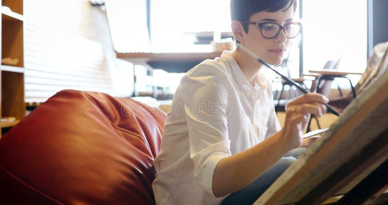 Δημιουργικός θηλυκός καλλιτέχνης που χρωματίζει τη νέα εικόνα στοκ φωτογραφίες