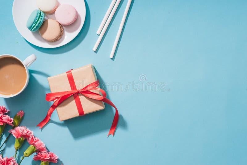 Δημιουργικός και macarons με το δώρο στο μπλε υπόβαθρο Τοπ όψη ΛΦ στοκ εικόνα με δικαίωμα ελεύθερης χρήσης