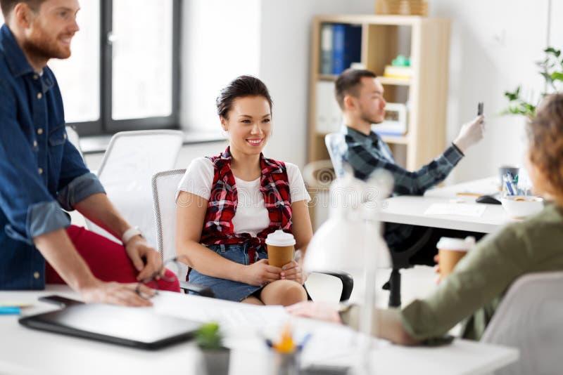 Δημιουργικός καφές κατανάλωσης ομάδων στο γραφείο στοκ εικόνες
