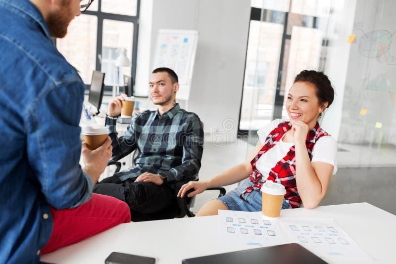 Δημιουργικός καφές κατανάλωσης ομάδων στο γραφείο στοκ φωτογραφία
