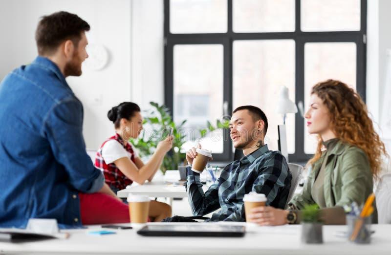 Δημιουργικός καφές κατανάλωσης ομάδων στο γραφείο στοκ φωτογραφίες