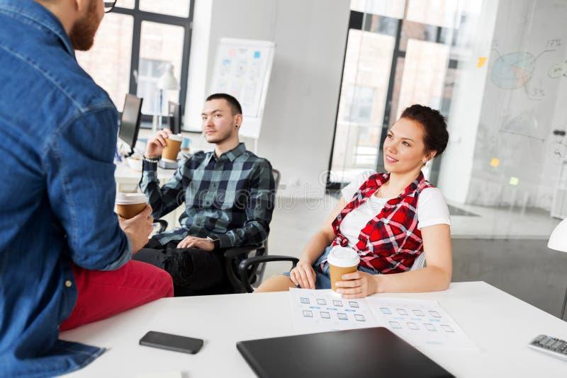 Δημιουργικός καφές κατανάλωσης ομάδων στο γραφείο στοκ εικόνα