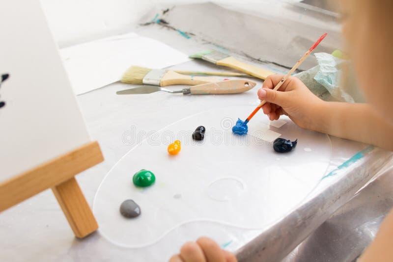 Δημιουργικός λίγος ζωγράφος στη διαδικασία εργασίας στοκ εικόνες