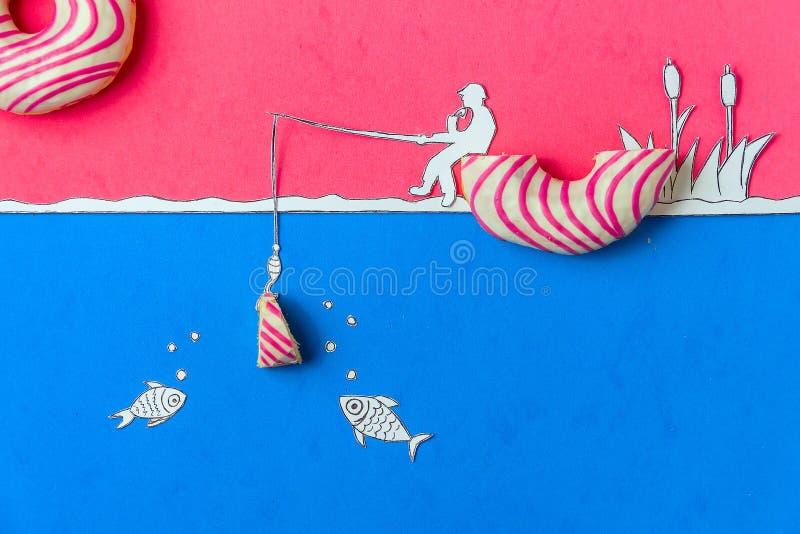 Δημιουργικός μινιμαλισμός τροφίμων, doughnut στη μορφή της βάρκας ενάντια στο ρόδινο ουρανό με τη τοπ άποψη Fishman, διάστημα αντ στοκ φωτογραφία