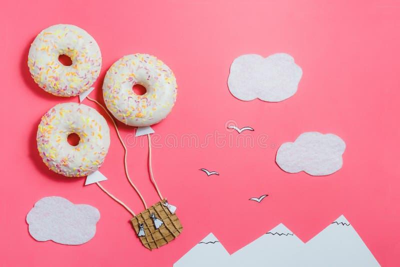 Δημιουργικός μινιμαλισμός τροφίμων, doughnut στη μορφή του αερόστατου στο ρόδινο ουρανό με τα σύννεφα, βουνά, τοπ άποψη, διάστημα στοκ εικόνες