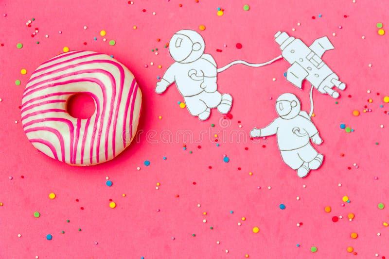 Δημιουργικός μινιμαλισμός τροφίμων, doughnut στη μορφή του πλανήτη στο ρόδινο ουρανό με τον αστροναύτη, τοπ άποψη διαστημικών σκα στοκ φωτογραφία με δικαίωμα ελεύθερης χρήσης