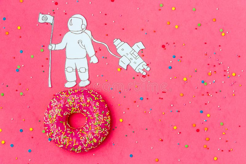 Δημιουργικός μινιμαλισμός τροφίμων, doughnut στη μορφή του πλανήτη στο ρόδινο ουρανό με τον αστροναύτη, τοπ άποψη διαστημικών σκα στοκ εικόνες με δικαίωμα ελεύθερης χρήσης