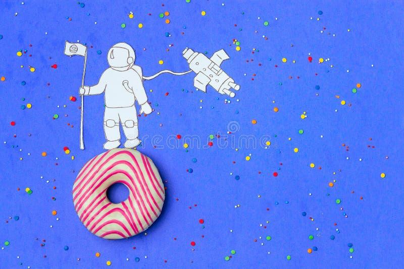 Δημιουργικός μινιμαλισμός τροφίμων, doughnut στη μορφή του πλανήτη στο μπλε ουρανό με τον αστροναύτη, τοπ άποψη διαστημικών σκαφώ στοκ φωτογραφία με δικαίωμα ελεύθερης χρήσης