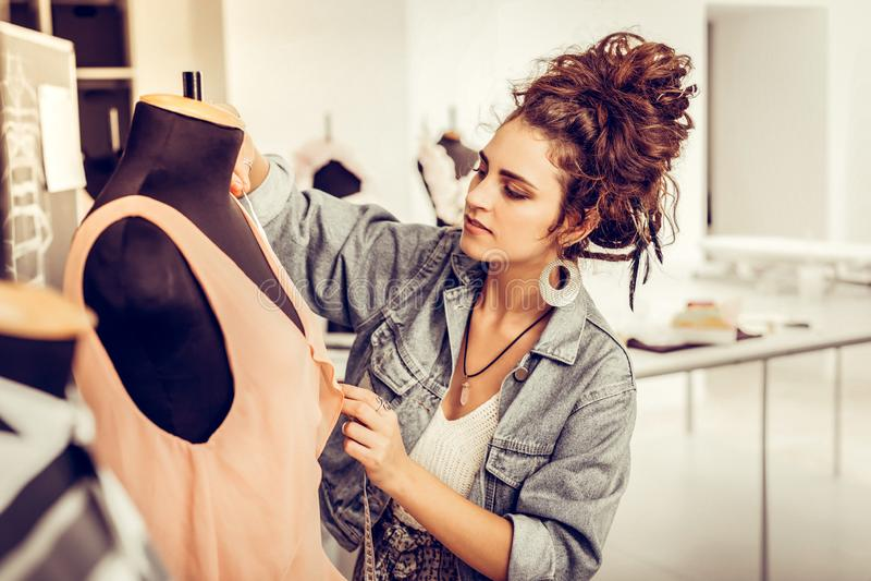 Δημιουργικός νέος σχεδιαστής που μετρά το όμορφο ροδάκινο-χρωματισμένο φόρεμα στοκ φωτογραφίες