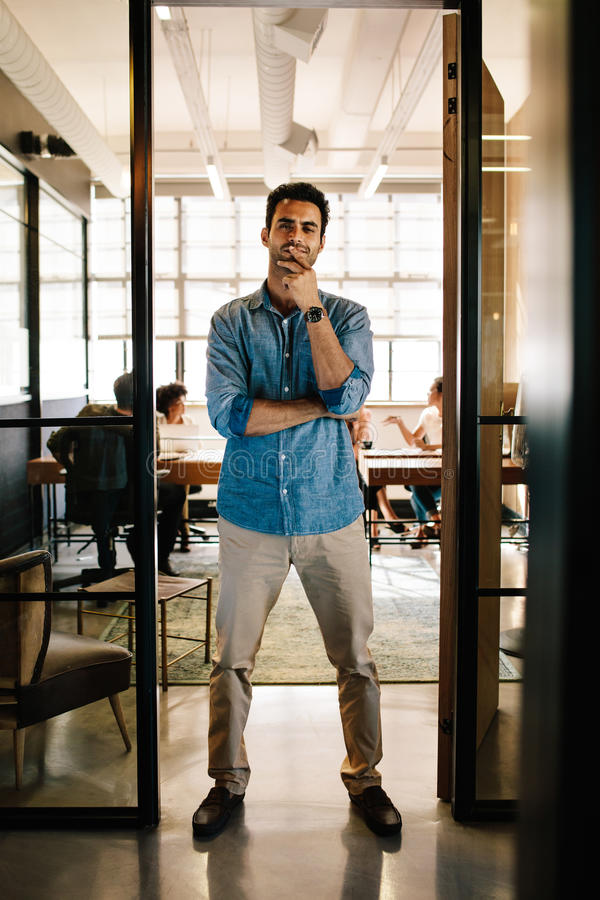 Δημιουργικός νεαρός άνδρας που στέκεται στην πόρτα στοκ φωτογραφία με δικαίωμα ελεύθερης χρήσης