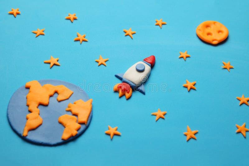 Δημιουργικός πύραυλος plasticine τεχνών στον ανοιχτό χώρο, όνειρα αστροναυτών Αστέρια, πλανήτης Γη και φεγγάρι Τέχνη κινούμενων σ στοκ φωτογραφία