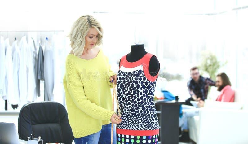 Δημιουργικός ράφτης που εργάζεται στην προσαρμογή του μοντέρνου φορέματος στοκ εικόνα με δικαίωμα ελεύθερης χρήσης