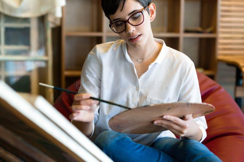 Δημιουργικός σκεπτικός σχολικός ζωγράφος τέχνης που εργάζεται στη ζωγραφική στοκ φωτογραφίες
