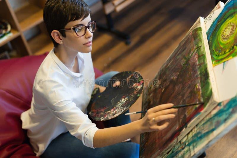 Δημιουργικός σκεπτικός σχολικός ζωγράφος τέχνης που εργάζεται στη ζωγραφική στοκ εικόνες