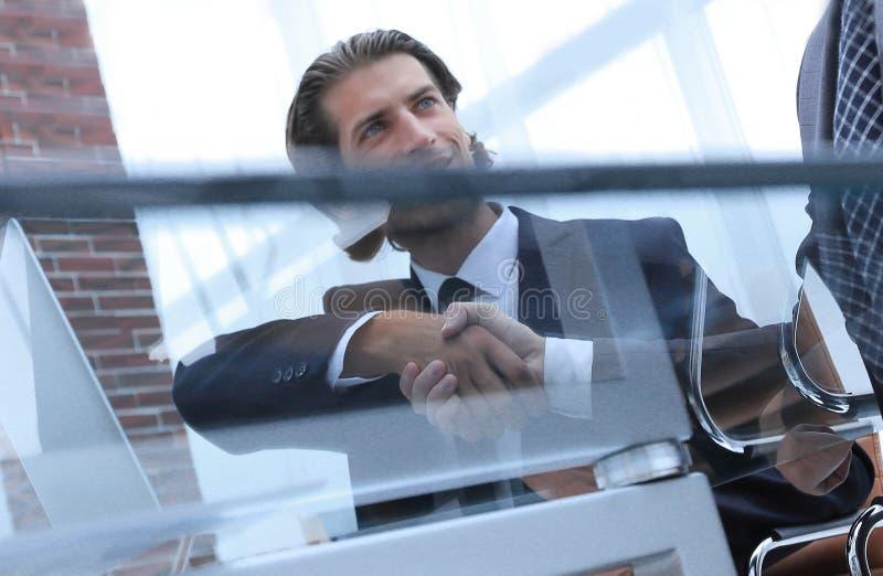 Δημιουργικός συνεργάτης χειραψιών, που κάθεται πίσω από ένα γραφείο στοκ φωτογραφία