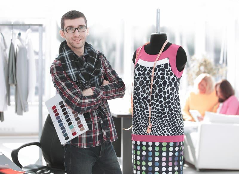 Δημιουργικός σχεδιαστής μόδας που στέκεται στο στούντιό του στοκ εικόνες