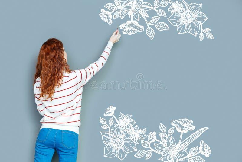 Δημιουργικός σχεδιαστής που διακοσμεί τον τοίχο και που φαίνεται συγκεντρωμένος στοκ φωτογραφία