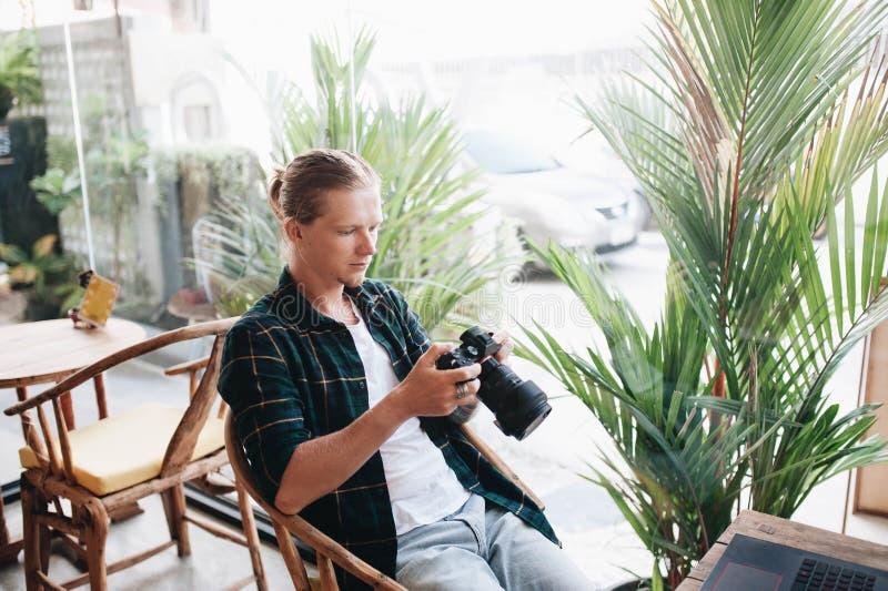 Δημιουργικός φωτογράφος που κρατά την επαγγελματική κάμερα, που κάθεται στον καφέ με το lap-top στοκ φωτογραφία με δικαίωμα ελεύθερης χρήσης