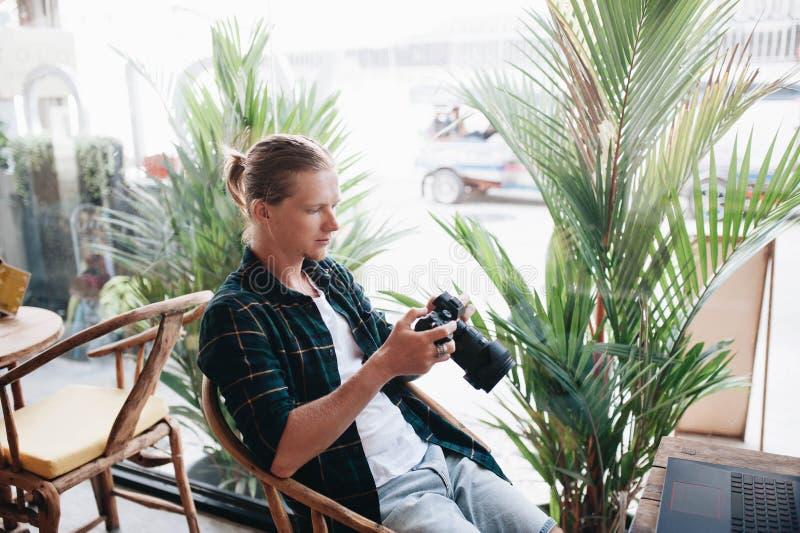 Δημιουργικός φωτογράφος που κρατά την επαγγελματική κάμερα, που κάθεται στον καφέ με το lap-top στοκ εικόνες με δικαίωμα ελεύθερης χρήσης