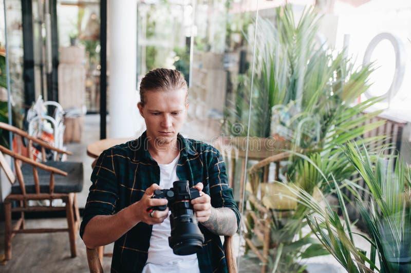 Δημιουργικός φωτογράφος που κρατά την επαγγελματική κάμερα, που κάθεται στον καφέ με το lap-top στοκ φωτογραφίες με δικαίωμα ελεύθερης χρήσης