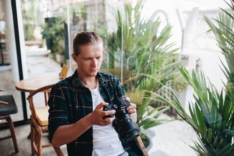 Δημιουργικός φωτογράφος που κρατά την επαγγελματική κάμερα, που κάθεται στον καφέ με το lap-top στοκ εικόνες