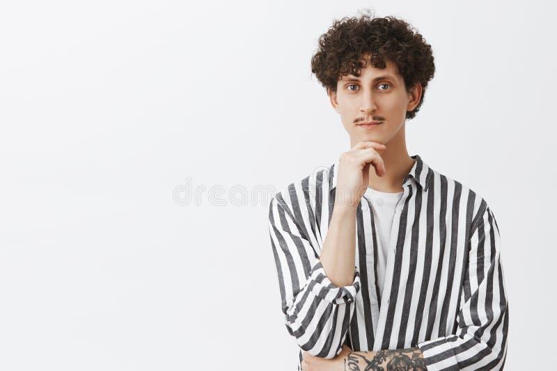 Δημιουργικός όμορφος εβραϊκός τύπος με τη σκοτεινή σγουρή τρίχα και moustache σχετικά με το πηγούνι και με περίεργο και ραδιουργη στοκ εικόνες με δικαίωμα ελεύθερης χρήσης