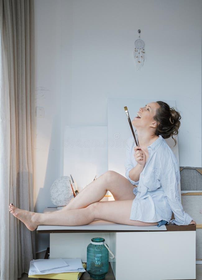 Δημιουργικός όμορφος ζωγράφος γυναικών μπροστά από τον καμβά και το σχέδιο στοκ φωτογραφίες με δικαίωμα ελεύθερης χρήσης