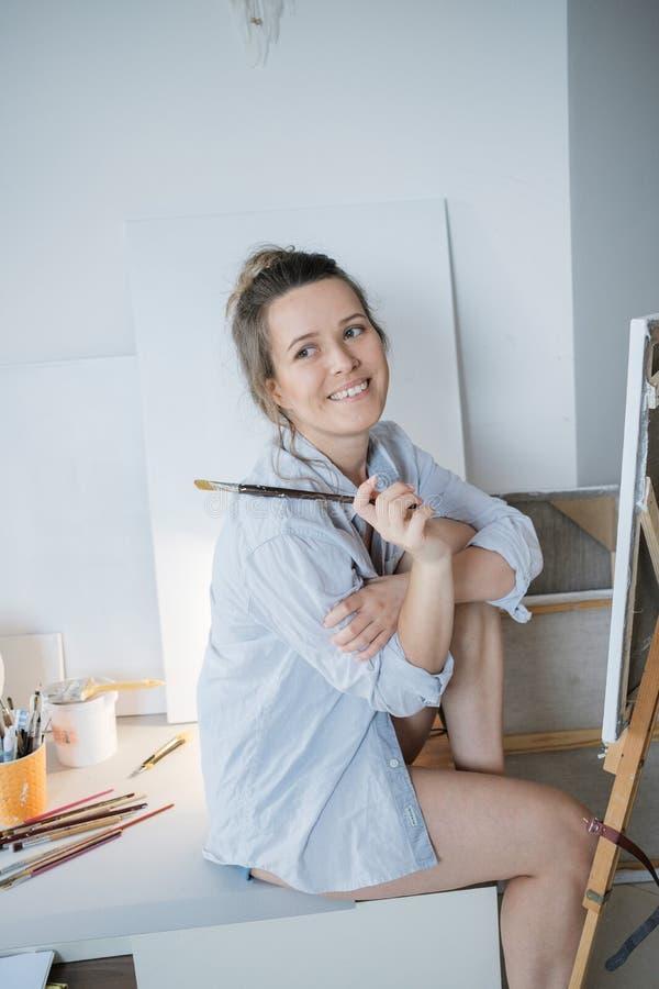 Δημιουργικός όμορφος ζωγράφος γυναικών μπροστά από τον καμβά και το σχέδιο στοκ εικόνες