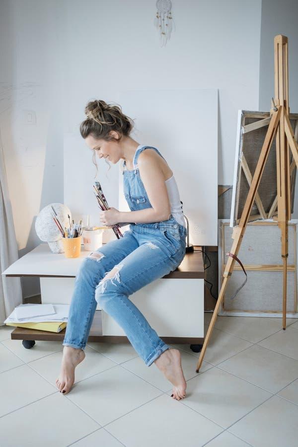 Δημιουργικός όμορφος ζωγράφος γυναικών μπροστά από τον καμβά και το σχέδιο στοκ εικόνα με δικαίωμα ελεύθερης χρήσης