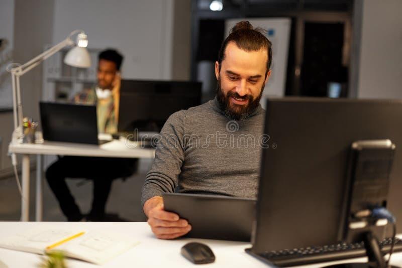 Δημιουργικό άτομο με τον υπολογιστή που λειτουργεί αργά στο γραφείο στοκ φωτογραφία με δικαίωμα ελεύθερης χρήσης