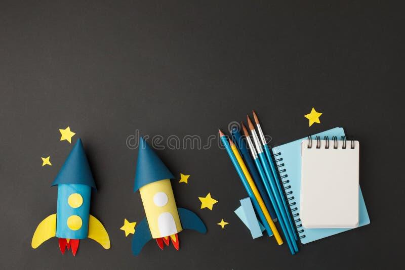 Δημιουργικό εκπαιδευτικό υπόβαθρο Επιστροφή στη σχολική έννοια πύραυλος κομμένος από χάρτινο σωληνάκι τουαλέτας και σχολικά εργαλ στοκ εικόνες