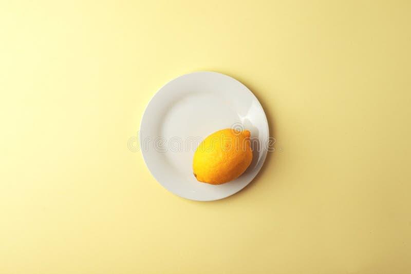 Δημιουργικό μονοχρωματικό θερινό σχεδιάγραμμα φιαγμένο από λεμόνι στο άσπρο πιάτο στο κίτρινο υπόβαθρο r στοκ εικόνες με δικαίωμα ελεύθερης χρήσης