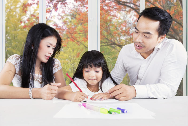 Δημιουργικό παιδί που μελετά με τους γονείς στο σπίτι στοκ εικόνες