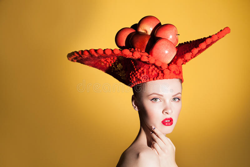 Δημιουργικό πορτρέτο ομορφιάς της νέας όμορφης γυναίκας που εξετάζει τη κάμερα και που θέτει στο στούντιο στο μεγάλο κόκκινο καπέ στοκ φωτογραφίες με δικαίωμα ελεύθερης χρήσης