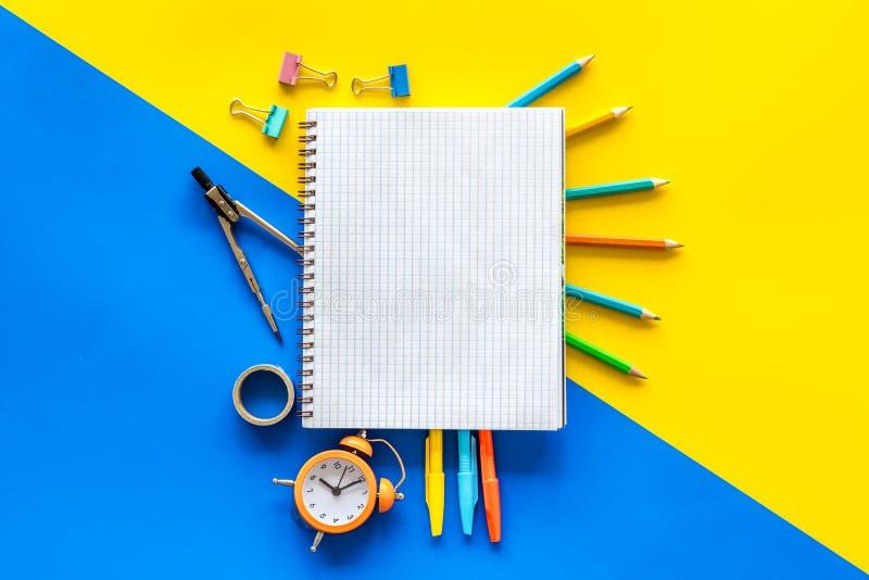 Δημιουργικό χάος στο γραφείο του μαθητή με κίτρινο και μπλε φόντο, πάνω μακέτα στοκ φωτογραφίες με δικαίωμα ελεύθερης χρήσης