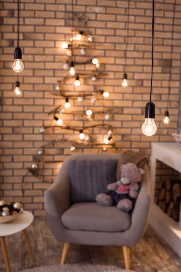 Δημιουργικό χριστουγεννιάτικο δέντρο, εστία και μεγάλη πολυθρόνα στο εσωτερικό σοφιτών στοκ φωτογραφίες