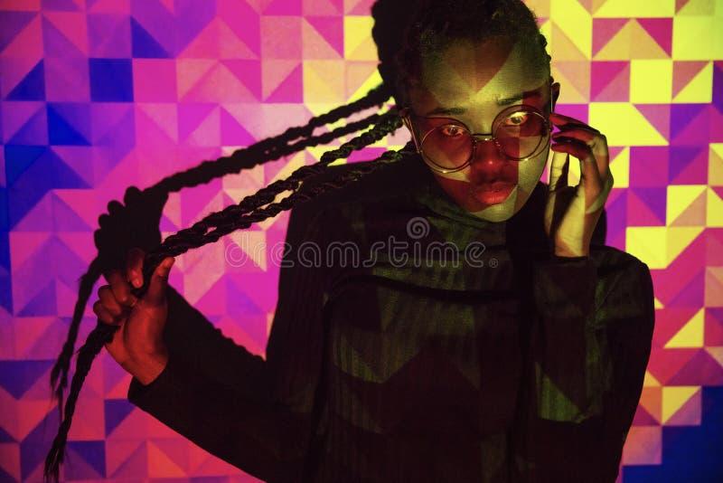Δημιουργικό χρωματισμένο σχέδιο από το φως προβολής στις όμορφες γυναίκες με το σκοτεινό δέρμα στοκ εικόνες